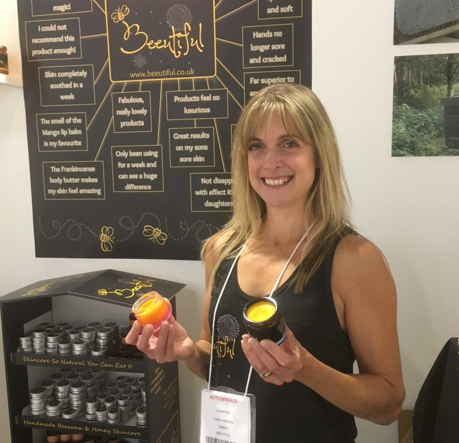 Carly Hooper holding beeswax and honey pots