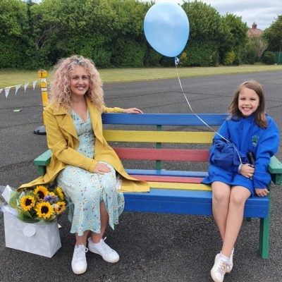 Michelle JOnes sitting on her Kindness bench